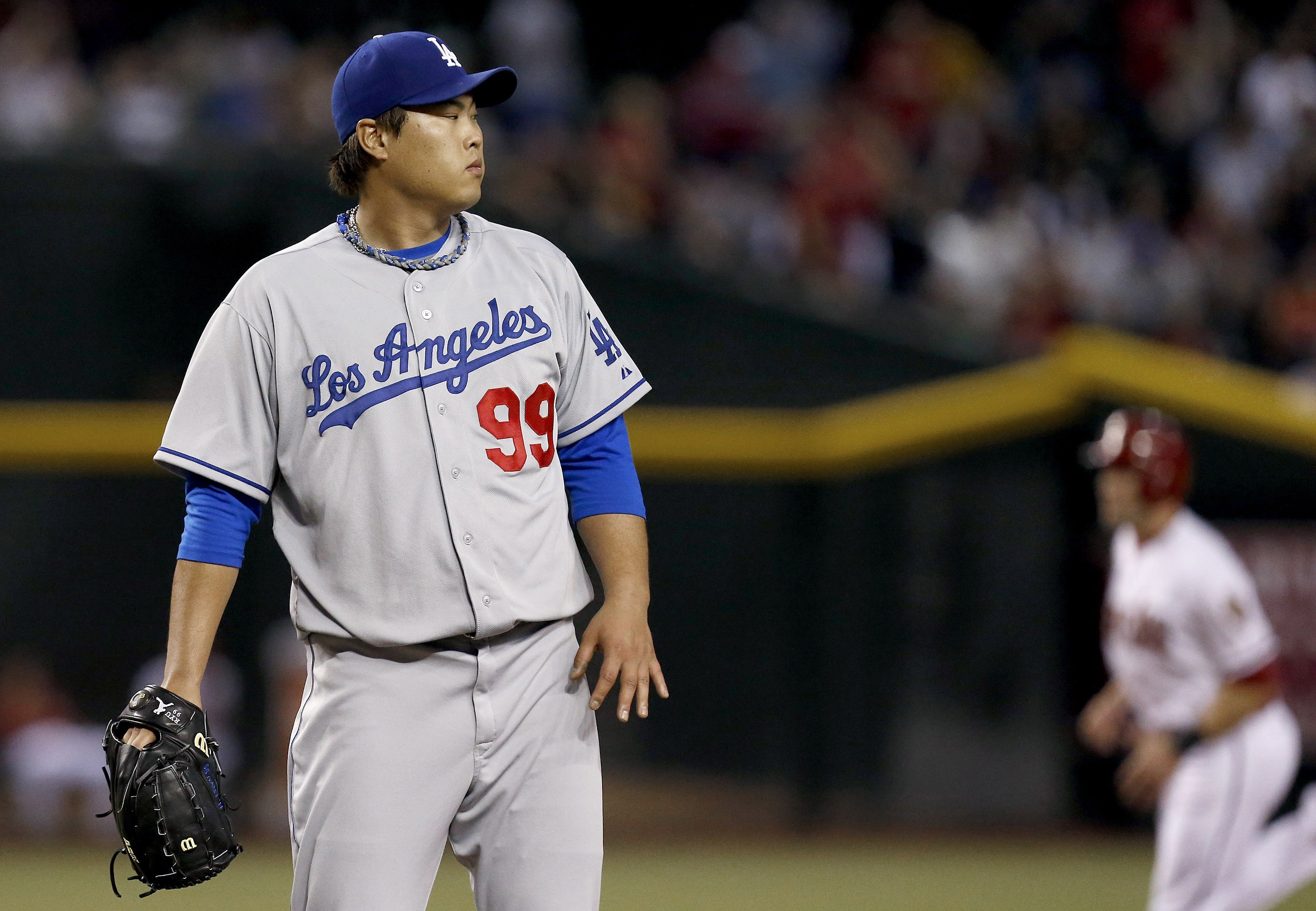 Los Angeles Dodgers' Hyun-Jin Ryu (99), of South Korea, looks at a Arizona Diamondbacks' Paul Goldschmidt two-run home run as Diamondbacks' A.J. Pollock, right, runs the bases in the first inning of a baseball game on Monday, Sept. 16, 2013, in Phoenix. (AP Photo/Ross D. Franklin)