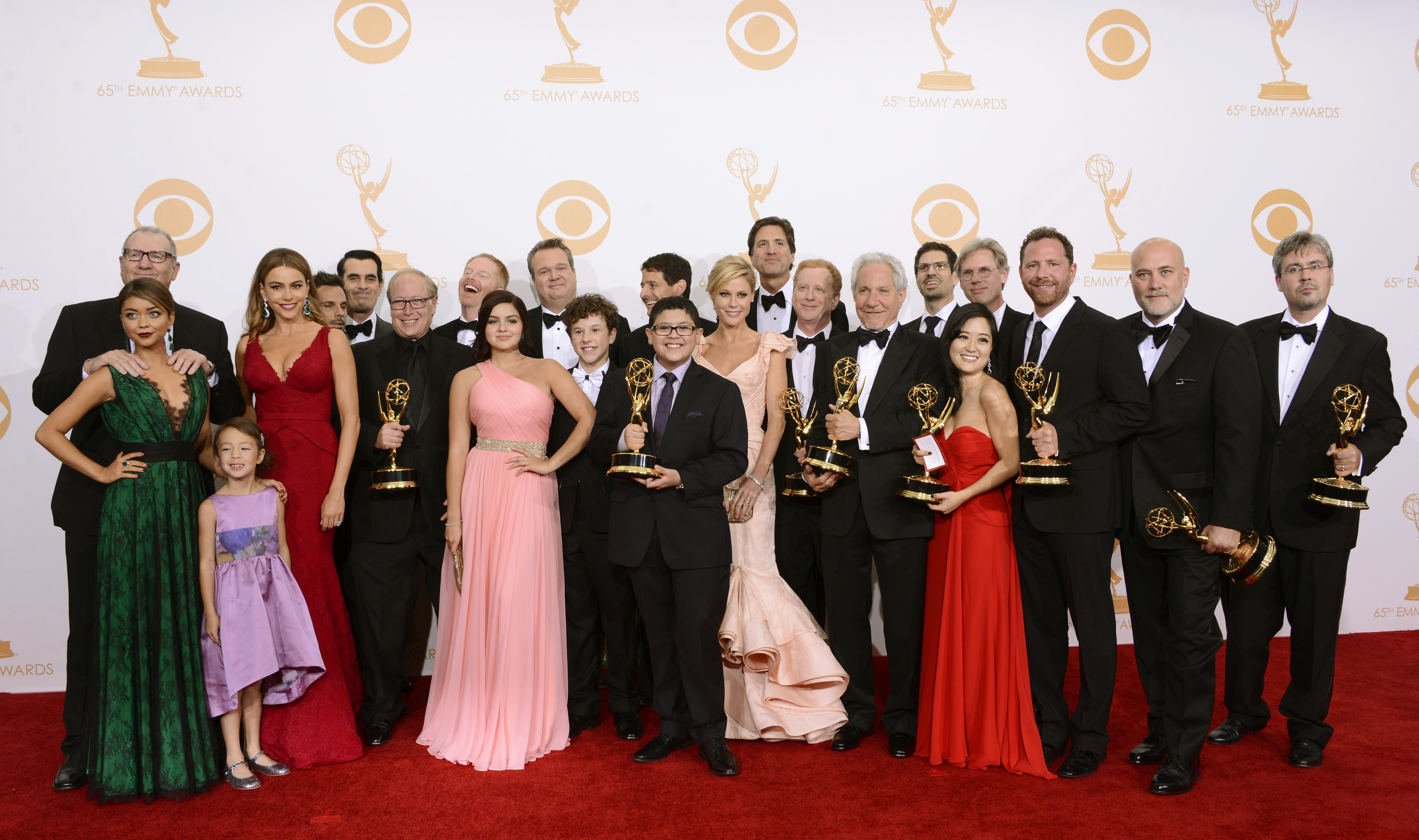 "Cast and crew from ""Modern Family"" pose with their Emmy for outstanding comedy series  backstage at the 65th Primetime Emmy Awards . Fourth from right is the  supervising producer Elaine Ko. (Photo by Dan Steinberg/Invision/AP)"