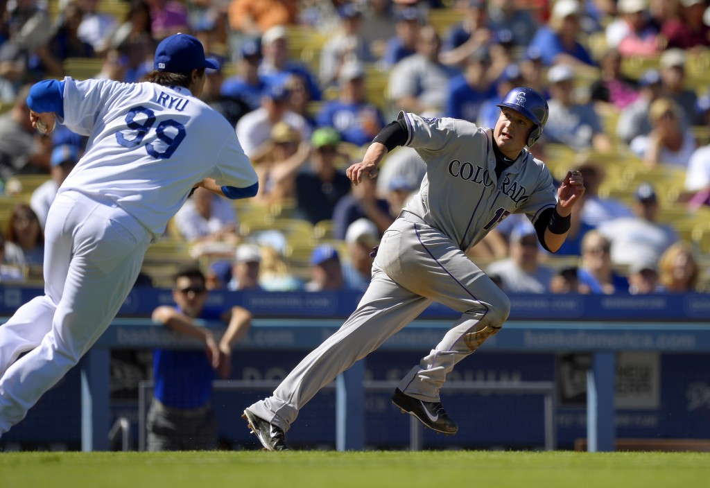 Los Angeles Dodgers starting pitcher Ryu Hyun-Jin, of South Korea, chases Colorado Rockies' Jordan Pacheco between third and home during a rundown in the fourth inning of a baseball game, Sunday, Sept. 29, 2013, in Los Angeles. Pacheco was tagged out on the play. (AP Photo/Mark J. Terrill)