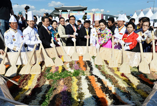 "Park Jin, fifth from left, president of the Asia Future Institute, poses with Peter Tan, sixth from left, the Singapore ambassador to Korea in a ""bibimbap"" mixing event held at Gwanghwamun Square, Wednesday. They are joined by Park Mi-young, fourth from right, promotional ambassador for Korean Food; James Person, fifth from left, a researcher at the U.S. Wilson Center; Kim Chae-yeon, fourth from left, Hansik promotional ambassador; and Kim Choong-yong, third from left, former councilor of Jongno-gu, Seoul.  /  Korea Times photo by Shim Hyun-chul"