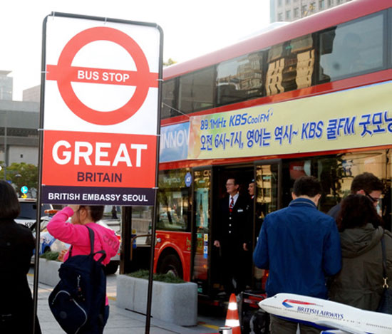 "British Airways staff stands on the steps of a double-decker ""routemaster"" at Gwanghwamun Square, Seoul, Friday.   / Korea Times photo by John Redmond"