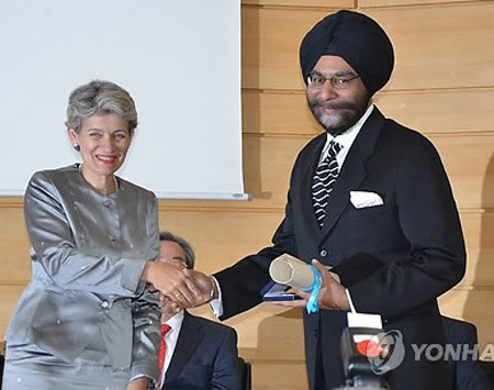 Director-General of UNESCO Irina Bokova, left, gives the UNESCO King Sejong Literacy Prize to an Indian representative from Saakshar Bharat (Literate India) Mission under the National Literacy Mission Authority (NLMA) at UNESCO headquarters in Paris, France, on Sept. 9. / Courtesy of Korean National Commission for UNESCO
