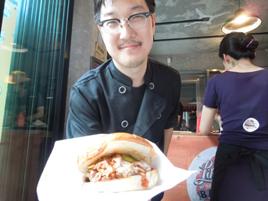 "Linus Kim of ""Linus' Bama Style Barbeque"" shows off a pulled pork sandwich."