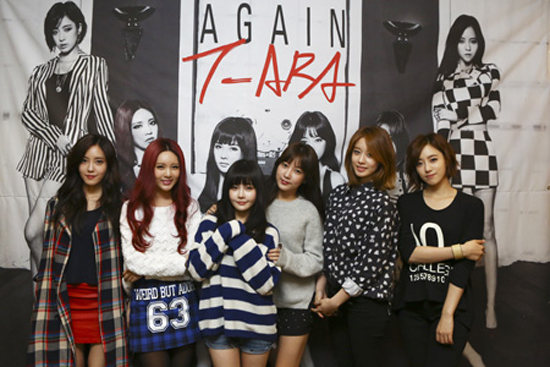 "From left, Hyomin, Qri, Boram, Soyeon, Jiyeon and Eunjung pose in front of a banner with the cover image of their latest album ""Again, T-ara"" in a café in Nonhyeon-dong, southern Seoul, Monday.  / Courtesy of Core Contents Media"