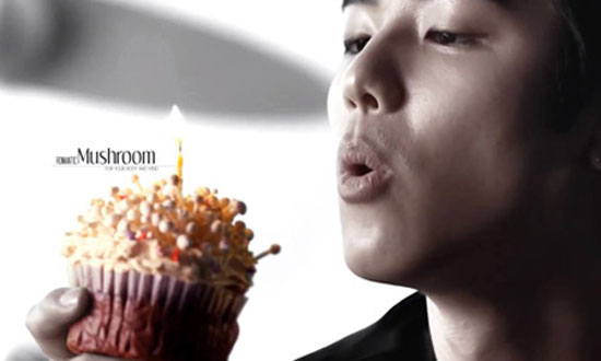 "Minhyuk, a member of K-pop group CNBLUE, blows out a candle on a cupcake of Enoki mushrooms in an advertisement for the Korea Agro-Fisheries and Food Trade promoting ""romantic mushrooms."" / Korea Times"