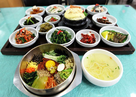 """Bibimbap,"" mixed-rice topped with vegetables, is served with side dishes. / Yonhap"