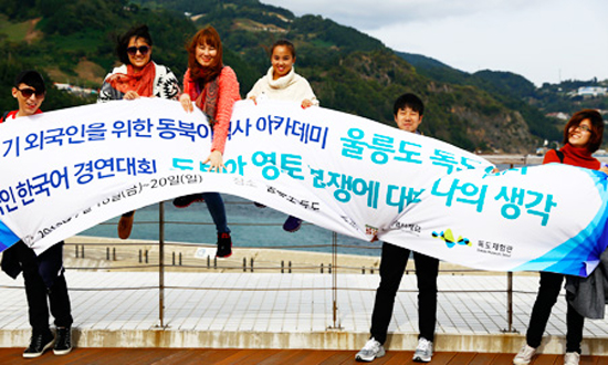 Foreign students from Mongolia, Ecuador, China and Singapore hold up a banner at Sadong Port on Ulleung Island, North Gyeongsang Province, Saturday, before embarking on a boat bound for Dokdo. The state-run Northeast Asian History Foundation arranged the field trip as part of its Northeast Asian history lectures for foreign students. / Korea Times photo by Yoon Sung-won