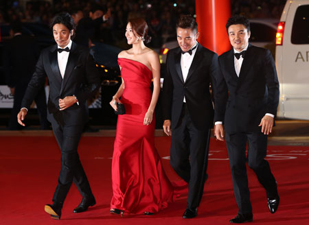 Actors Kim Min-jun, So E-hyun, Uhm Tae-woong, and actor-turned director Park Joong-hoon, from left, walk the red carpet during the festival's opening ceremony, Thursday. / Yonhap
