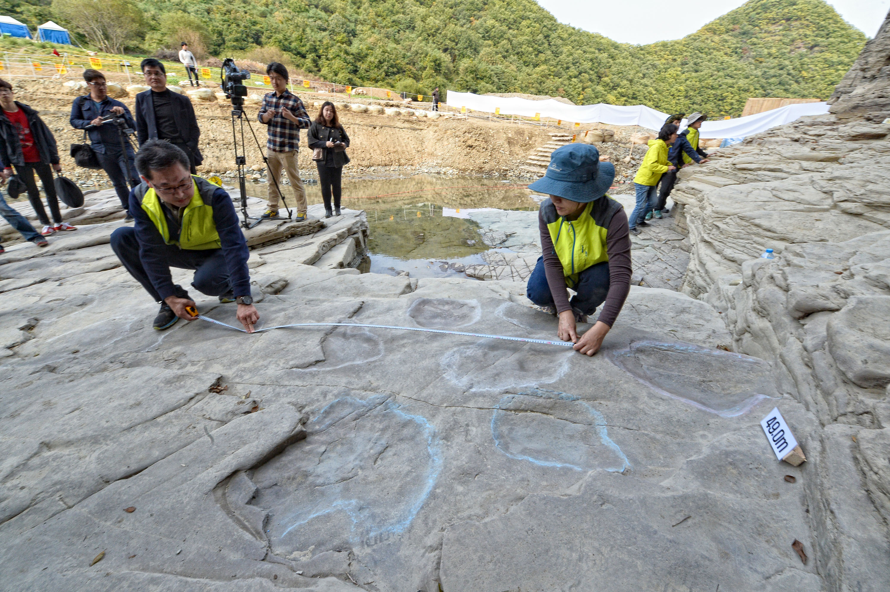 This photo shows 25 fossilized dinosaur footprints recently discovered by researchers on a rock near the site along a tributary of a river in Ulsan where the construction of a dike-like movable dam is under way to better preserve a set of prehistoric engravings from being eroded in floodwater. (Yonhap)