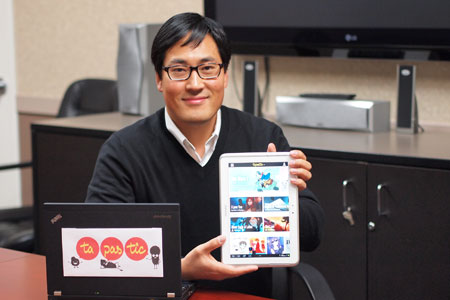Kim Chang-won, CEO of Tapasmedia, which is the first online platform for web comics in the North American market, points out scenes of a webtoon displayed on a tablet PC.  / Courtesy of Tapasmedia