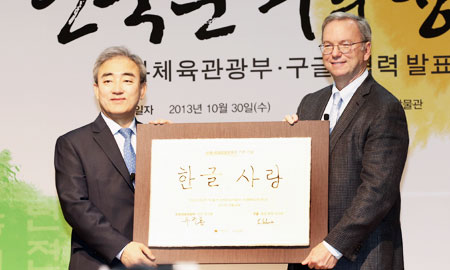 "Google Executive Chairman Eric Schmidt, right, poses with Culture, Sports and Tourism Minister Yoo Jin-ryong after the Internet giant signed an agreement with the government, Wednesday, to help the country promote ""hangeul,"" the Korean alphabet. / Yonhap"