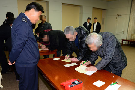 "South Korean ""defectors"" handed over by North Korea, Friday, go through entry procedures at the truce border village of Panmunjeom in Paju, Gyeonggi Province. / Courtesy of Ministry of Unification"