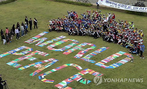 "A group of visiting descendants of foreign soldiers who participated in the 1950-53 Korean War makes the phrase ""WORLD PEACE' with their national flags at a square near the U.N. Memorial Park in South Korea's largest port city of Busan on the occasion of the 68th United Nations Day on Oct. 24, 2014. Soldiers from 16 nations fought for South Korea against invading North Korea under the U.N. flag during the war. (Yonhap)"