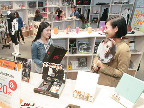 "Visitors to ""with DRAMA"" at Lotte FITIN in Dongdaemun hold up hallyu products. / Courtesy of Lotte FITIN"