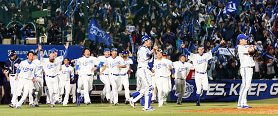 The Samsung Lions rush the field after pitcher Oh Seung-hwan recorded the final out against the Doosan Bears in Game Seven of the Korean Series at Daegu Stadium, Friday. The Lions won 7-3, capturing their third title in as many years. / Yonhap