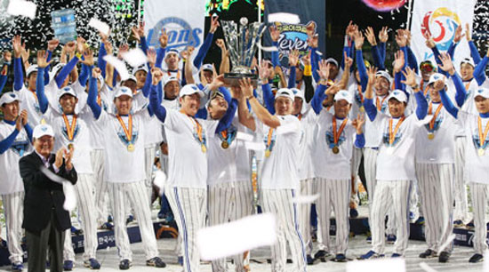 Samsung Lions players celebrate holding the trophy after beating the Doosan Bears 7-3 to capture the Korean Series in seven games at Daegu Stadium, Friday. They became the first team to claim three consecutive Korean Baseball Organization championships. / Yonhap