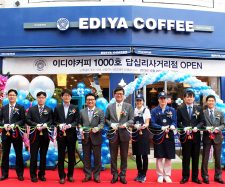 Moon Chang-ki, center, CEO of Ediya Coffee, cuts the ribbon with company employees during an opening ceremony for Ediya's 1,000th store in Dongdaemun-gu, Seoul, Oct. 29, 2013.