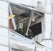 Workers engage in repair work Monday at a 38-story I'Part apartment in Samseong-dong, southern Seoul, into which a Sikorsky helicopter owned by LG Electronics crashed on Saturday, killing the two pilots onboard. Concerns over safety in high-rise apartments in the capital are rising after the accident.