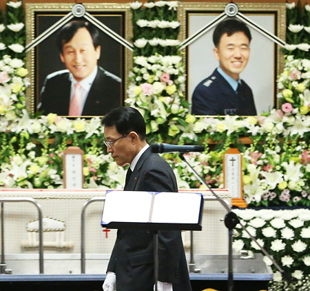 LG Electronics Vice President Nam Sang-geon walks past the photographs of the company's two helicopter pilots — Park In-kyu and Koh Jong-jin — before making a address at their memorial service at Asan Medical Center in southern Seoul, Tuesday. The two pilots were killed during a flight from Gimpo International Airport to the Jamsil Heliport after their helicopter crashed into an I'Park apartment in Samseong-dong, southern Seoul, Saturday, in heavy fog. / Yonhap