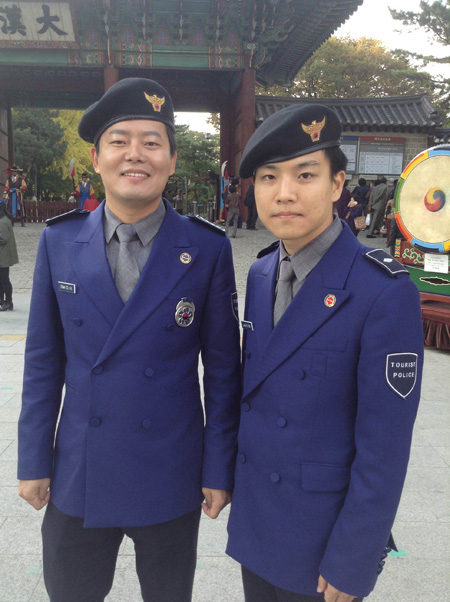 Sgt. Shin Chang-hoon, left, a tourist police officer, poses with his colleague Lee Kyung-min in front of Deoksu Palace while patrolling the area last month. / Korea Times photo by Kwon Ji-youn