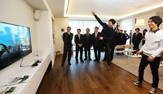 Microsoft Korea workers play a motion-capture game at the firm's new head office in Gwanghwamun, Seoul, Tuesday. Watching them are U.S. Ambassador to Korea Sung Kim, left, and Microsoft Korea CEO Kim James Woo, second from left. / Yonhap