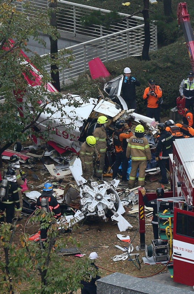 The firefighters on Saturday investigate the wreckages a site where a helicopter fell down after crashing into an apartment building in Samsung-dong, Seoul. (Yonhap News)