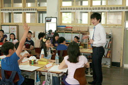 A certified public accountant of Samil PricewaterhouseCoopers teaches market economy for one day to elementary school students in Seoul on May 23, 2013.