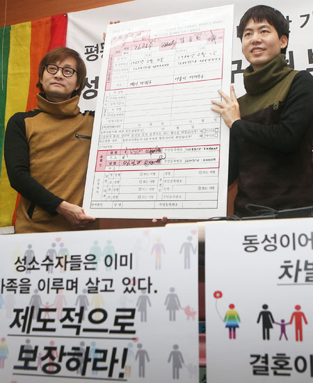 Movie director Kim-Jho Kwang-soo, left, 48, and his partner Kim Seung-hwan hold a blown-up copy of a marriage registration form during a press conference at which they urged the government to recognize their union at the office of the People's Solidarity for Participatory Democracy in central Seoul, Tuesday. They sent their marriage registration form to Seodaemun District Office, but the office said it will not accept it. (Yonhap)