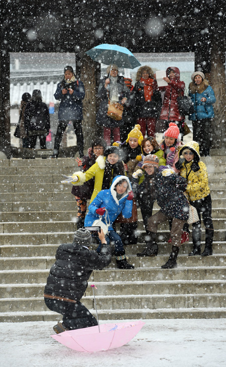 Foreign travelers enjoy the Hanok Village in Mt. Nam, Seoul, on a snowy day earlier this month. (Korea Times photo by Shim Hyun-chul)