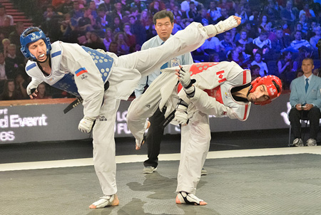 Russia's Alexey Denisenko, left, and Canada's Maxime Potvin exchange kicks during the men's under-68-kilogram final match on the third and last day of the inaugural WTF World Taekwondo Grand Prix at the Manchester Central Convention Complex in Manchester, the United Kingdom, Monday (KST). Denisenko won to earn his country the gold medal. With no medals added on Monday, Korea finished a surprising sixth among 59 nations, without producing a single gold medalist. / Courtesy of WTF