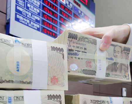 undles of 10,000-yen banknotes are stacked in front of an electronic billboard showing real-time currency exchange rates at a Korea Exchange Bank branch in Seoul, Monday. The Japanese yen fell below 1,000 won per 100 yen for the first time since Sept. 9, 2008. (Yonhap)