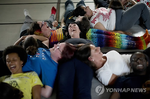 People laugh as they take part in performing a group exercise during a laughter yoga class in St. Albans, England on Sunday, June 9, 2013. (AP Photo/ yonhap)