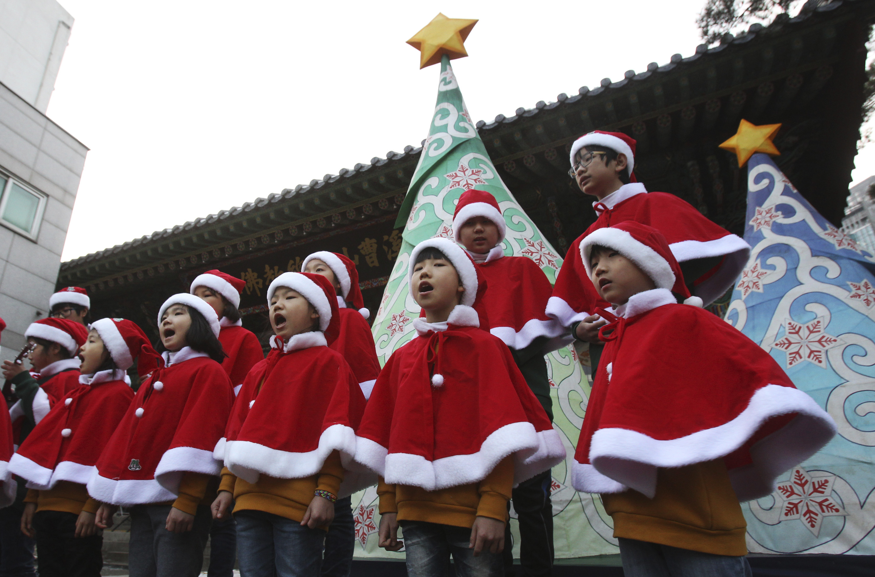 Buddhist children wearing Santa Claus costumes sing Christmas songs in a ceremony to celebrate upcoming Christmas at the Chogye temple in Seoul, South Korea, Wednesday, Dec. 18, 2013. South Korean Buddhists have been celebrating Christmas to show their goodwill toward Christians.(AP Photo/Ahn Young-joon)