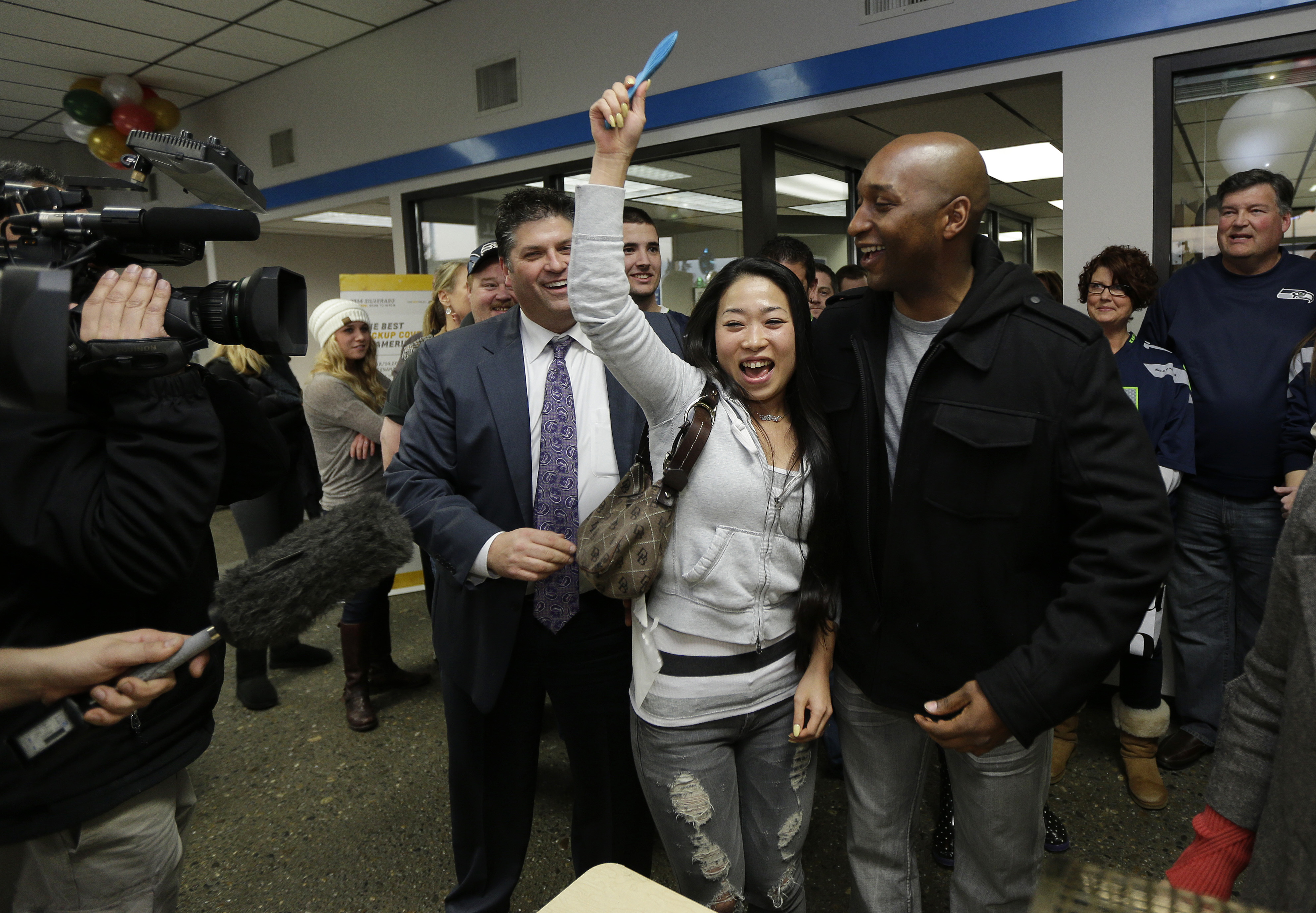 Yujin Oliver, the woman in the middle, and her husband Samonie Oliver, right, are celebrating next to Mike Gates, left, general manager of Jet Chevrolet in Federal Way, Wash., Monday, Dec. 16, 2013, after their ticket was drawn as one of 12 $35,000 winners in a dealership-sponsored raffle held only if the Seattle Seahawks shut out the New York Giants in last Sunday's NFL football game. The Seahawks defeated the Giants 23-0, and the winners drawn Monday will soon be receiving checks from the insurance policy purchased by the dealership to fund the drawing. (AP Photo/Ted S. Warren)