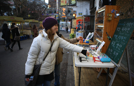 A foreign traveler examines items at an accessory shop in the leisure district of Jongno, Seoul.  (Courtesy of Korea Tourism Organization)