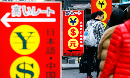 Tourists pass by a currency exchange signboard in the shopping district of Myeong-dong, downtown Seoul, Sunday. (Yonhap)