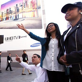Visitors look at a banner promoting the world's first curved ultra high-definition (UHD) TV manufactured by Samsung Electronics at the Las Vegas Convention Center, Monday (KST). (Courtesy of Samsung Electronics)