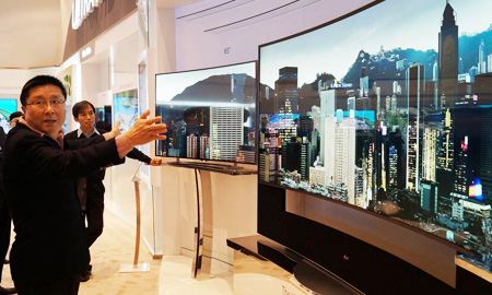 LG Display CEO Han Sang-beom checks out details of its massive 105-inch curved LCD TV at the firm's booth at the Bellagio Hotel on the Las Vegas strip, Monday (KST). (Courtesy of LG Display)