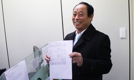 Kim Seong-do, 74, holds a receipt for the value-added tax the Dokdo resident paid for what he earned from the sale of Dokdo-related souvenirs last year, at the National Tax Service, Monday. (Courtesy of NTS)