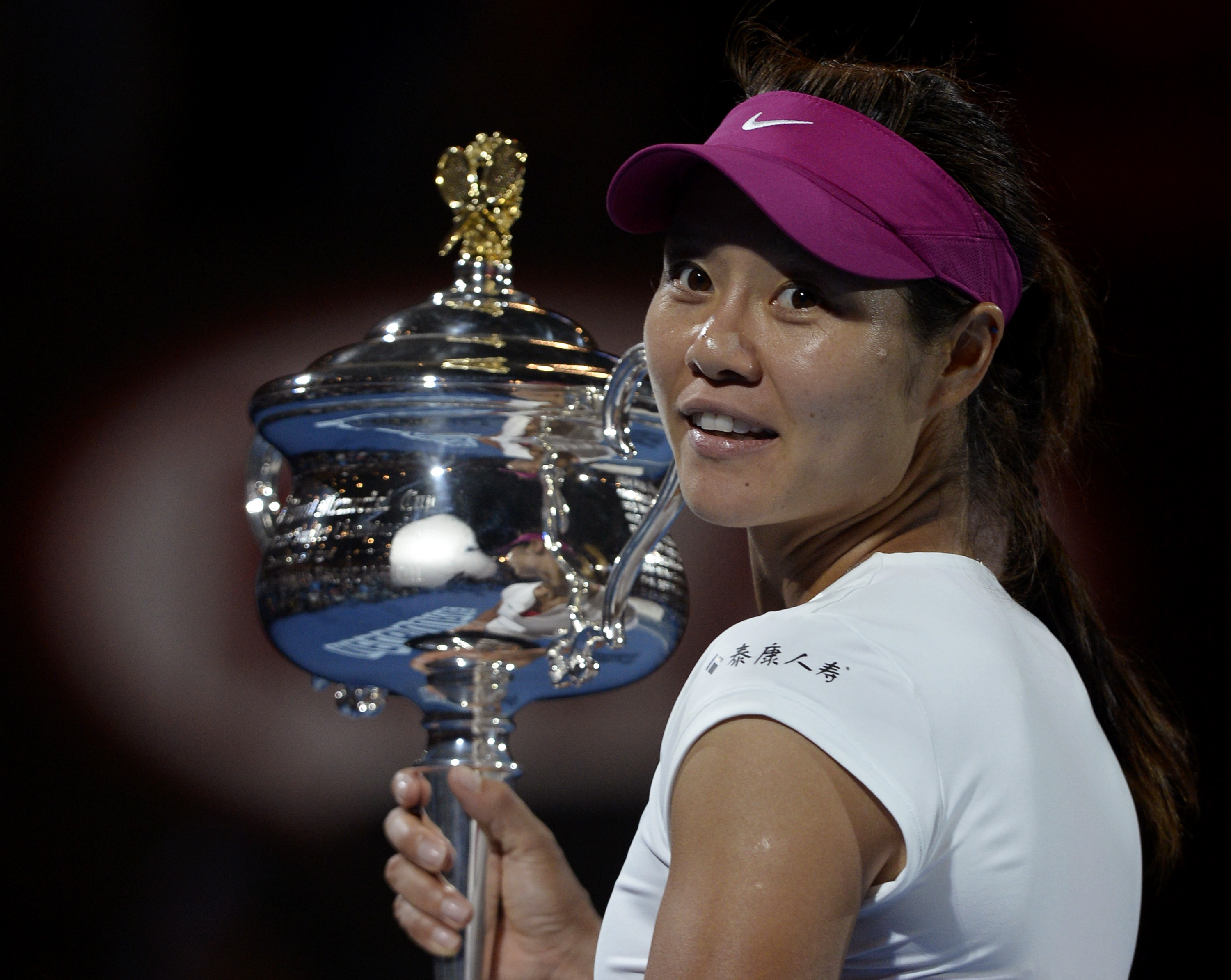 Li Na of China holds the championship trophy after defeating Dominika Cibulkova of Slovakia in their women's singles final at the Australian Open tennis championship in Melbourne, Australia, Saturday, Jan. 25, 2014.(AP Photo/Andrew Brownbill)