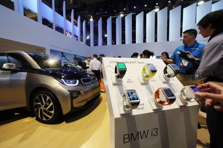 Samsung Electronics' Galaxy Gear smartwatches are on display at the booth of BMW along with the automaker's i3 electric vehicle at the 2014 International Consumer Electronics Show. (Yonhap)