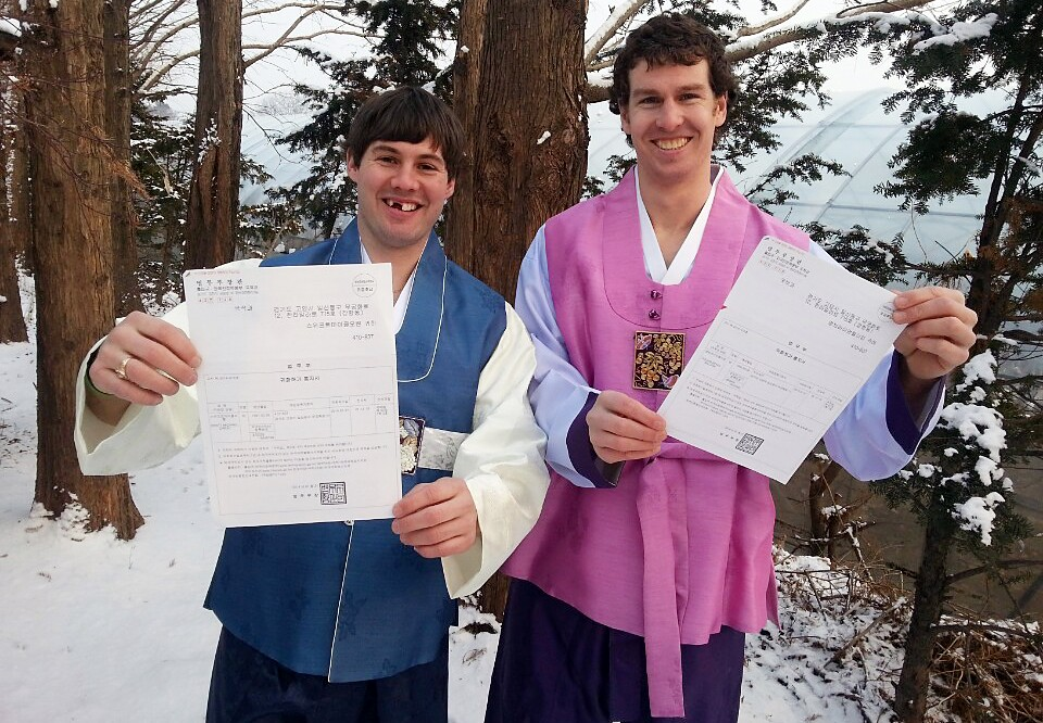 Canadian ice hockey players Michael Swift, left, and Brian Young smile as they hold up Korean citizenship papers earlier this year. (Yonhap)