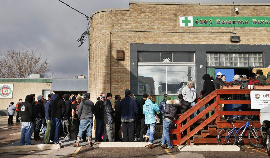 "Customers stand in line shortly after the opening of 3D Cannabis Center, which opened as a legal recreational retail outlet in Denver at 8am on Wednesday Jan. 1, 2014. Colorado began retail marijuana sales on Jan. 1, a day some are calling ""Green Wednesday."" (AP Photo/Brennan Linsley)"
