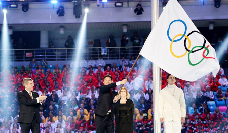 International Olympic Committee President Thomas Bach, left, applauds as Lee Seok-rai, mayor of Pyeongchang, waves the Olympic flag during the closing ceremony of the 2014 Winter Olympics in Sochi, Russia, Sunday. (Yonhap)