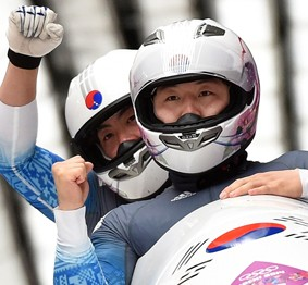 Two-man bobsleigh team pilot Won Yun-jong, left, and brakeman Seo Young-woo react as they cross the finish line in their final run at the Sochi Olympics at the Sanki Sliding Center, Monday. The team finished 18th overall, the highest ever for Korean bobsledders. (AP-Yonhap)