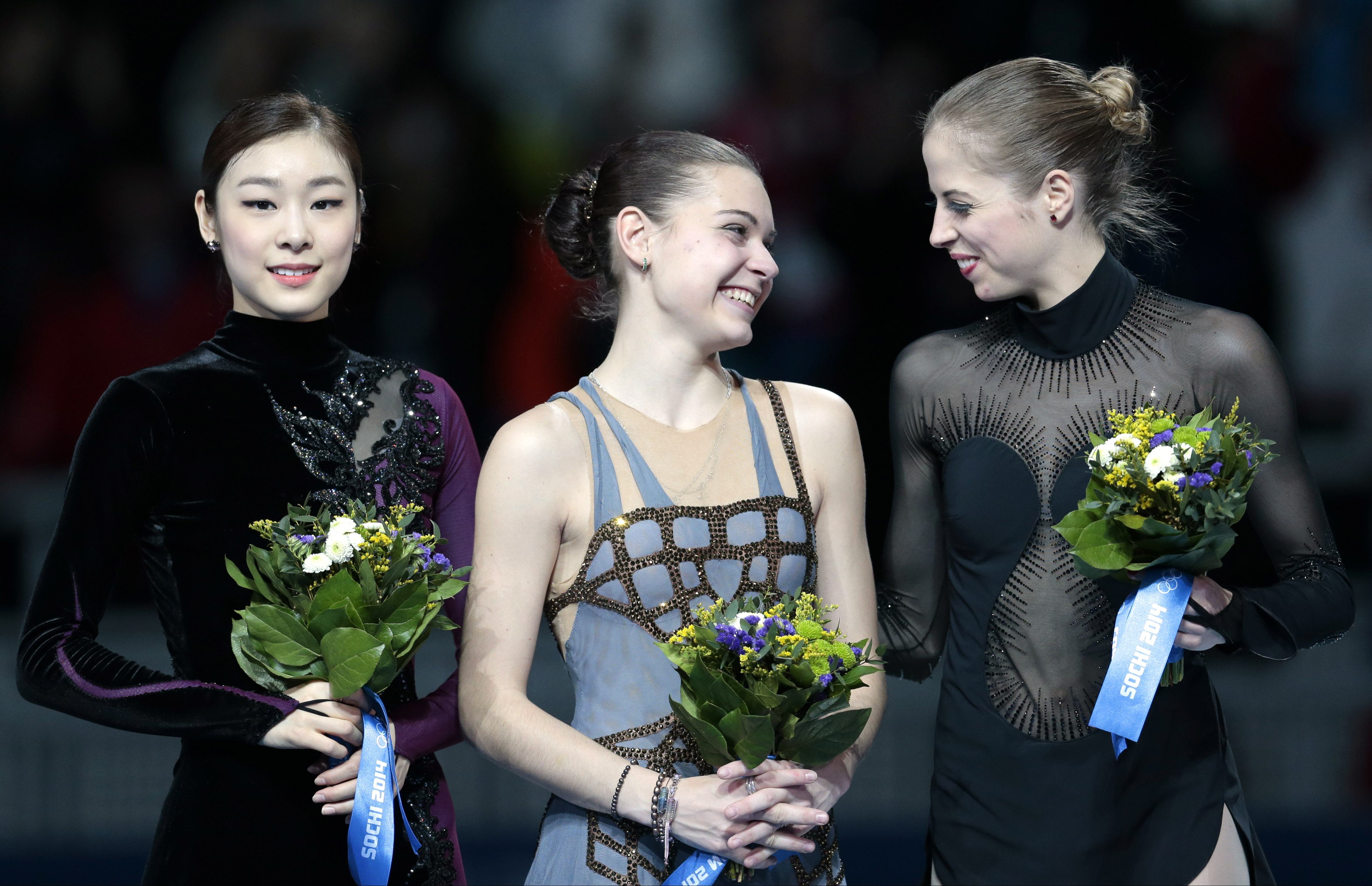 Adelina Sotnikova of Russia, centre, Kim Yuna of South Korea, left, and Carolina Kostner of Italy stand on the podium during the flower ceremony for the women's free skate figure skating final at the Iceberg Skating Palace during the 2014 Winter Olympics, Thursday, Feb. 20, 2014, in Sochi, Russia. Sotnikova placed first, followed by Kim and Kostner. (AP Photo/Ivan Sekretarev)