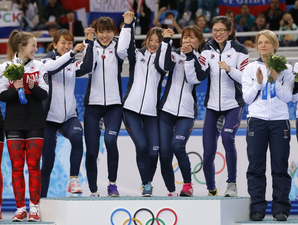 The South Korean team, centre, celebrate on the podium during the flower ceremony for the women's 3000m short track speedskating relay final at the Iceberg Skating Palace during the 2014 Winter Olympics, Tuesday, Feb. 18, 2014, in Sochi, Russia. (AP Photo/Vadim Ghirda)