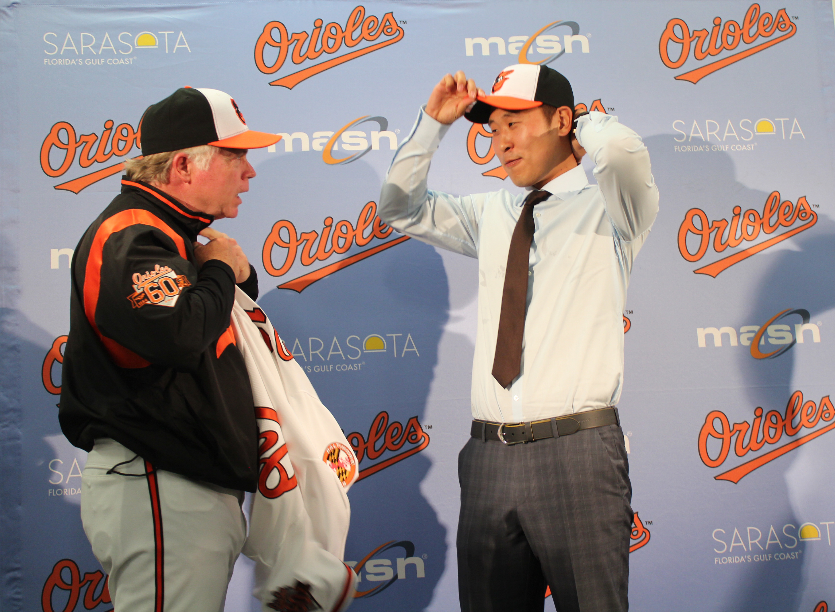 Korean pitcher Yoon Suk-min, right, puts on the Baltimore Orioles cap, while the Orioles manager Buck Showalter waits to help him put on his new uniform jersey. (Yonhap)