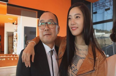 """Model and actress Clara, right, whose real name is Lee Sung-min, drapes her arm around her father's neck in the top photo captured from a TV show aired on Nov. 4. Her father, Lee Seung-kyu, is the lead vocalist of singing group Koreana, which sang the theme song """"Hand in Hand"""" at the 1988 Seoul Olympics."""