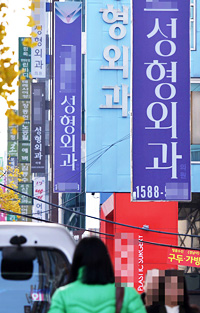 People walk down a street lined with cosmetic surgery clinics in Apgujeong-dong in Seoul. The clinics shown in the photo are not related to this article. (Korea Times file)